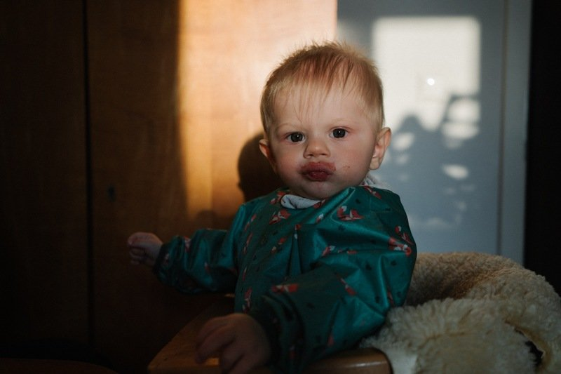 Baby mit verschmiertem Mund schaut in die Kamera familienfotografie