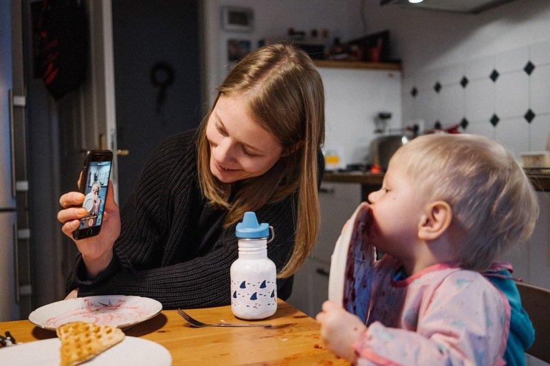 Mutter zeigt Sohn was auf dem smartphone natürliche familienfotografie